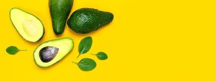 Ώριμα τεμαχισμένα φύλλα αβοκάντο και σπανακιού στην κίτρινη τοπ άποψη υποβάθρου Το δημιουργικό επίπεδο σύνθεσης τροφίμων βρέθηκε  στοκ φωτογραφία με δικαίωμα ελεύθερης χρήσης