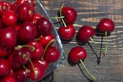 ώριμα φρούτα κερασιών μούρων σε ένα βάζο γυαλιού σε ένα σκοτεινό ξύλινο υπόβαθρο Στοκ Εικόνες