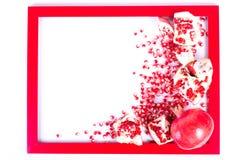 Ώριμα φρούτα ροδιών, σπόροι σε ένα κόκκινο πλαίσιο που απομονώνεται Στοκ Εικόνα
