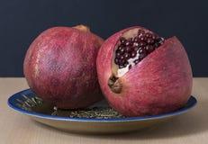 Ώριμα φρούτα ροδιών στο εκλεκτής ποιότητας πιάτο και τη διακοπή Στοκ Εικόνες