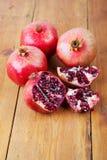 Ώριμα φρούτα ροδιών τέσσερα στην ξύλινη επιφάνεια Στοκ Φωτογραφία