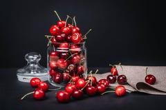 Ώριμα juicy κεράσια σε ένα γυαλί σε ένα σκοτεινό υπόβαθρο Στοκ Φωτογραφίες