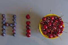Ώριμα juicy κεράσια στο πιάτο και τη λέξη ` γεια ` που σχεδιάζονται από τα μούρα των σταφυλιών και των κερασιών στοκ εικόνες με δικαίωμα ελεύθερης χρήσης