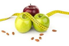 Ώριμα juicy μήλα, αμύγδαλα, και μέτρο ταινιών στοκ φωτογραφία