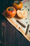 Ώριμα persimmons στον ξύλινο πίνακα με την κανέλα στοκ εικόνα