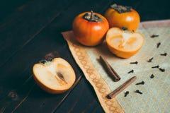 Ώριμα persimmons στον ξύλινο πίνακα με την κανέλα στοκ εικόνες με δικαίωμα ελεύθερης χρήσης