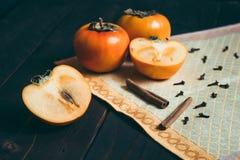 Ώριμα persimmons στον ξύλινο πίνακα με την κανέλα στοκ φωτογραφία με δικαίωμα ελεύθερης χρήσης