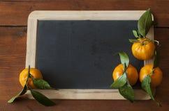Ώριμα tangerines με πράσινο βγάζουν φύλλα Στοκ Φωτογραφία