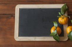 Ώριμα tangerines με πράσινο βγάζουν φύλλα Στοκ Εικόνα