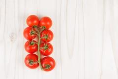 Ώριμες κόκκινες ντομάτες στην άμπελο σε μια άσπρη ξύλινη επιφάνεια Τοπ όψη Στοκ Φωτογραφία