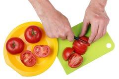Ώριμες κόκκινες περικοπές αρχιμαγείρων κουζινών ντοματών ηλικιωμένες με ένα αιχμηρό μαχαίρι Στοκ Εικόνες