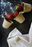 Ώριμες, κόκκινες φράουλες, άσπρη πετσέτα λινού και κονιοποιημένος, ζάχαρη τήξης στο σκοτεινό υπόβαθρο r στοκ εικόνες με δικαίωμα ελεύθερης χρήσης