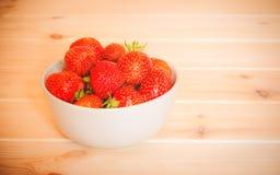 Ώριμες κόκκινες φράουλες στο άσπρο κύπελλο στον ξύλινο πίνακα Στοκ εικόνα με δικαίωμα ελεύθερης χρήσης