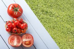 Ώριμες ντομάτες κερασιών στο ψάθινο καλάθι και την τεμαχισμένη ντομάτα στον ξύλινο πίνακα σε υπαίθριο Τοπ όψη Χλόες για το διάστη στοκ φωτογραφίες