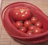 Ώριμες ντομάτες σε ένα κόκκινο καλάθι Στοκ Φωτογραφίες