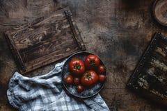 Ώριμες ντομάτες στο πιάτο ξύλινο tabletop Στοκ εικόνα με δικαίωμα ελεύθερης χρήσης