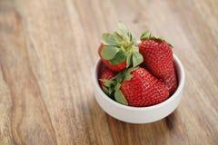 Ώριμες οργανικές φράουλες στο άσπρο κύπελλο στον ξύλινο πίνακα Στοκ Εικόνες
