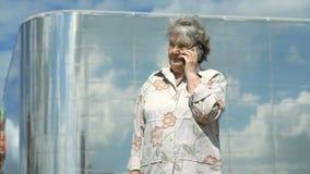 Ώριμες συζητήσεις ηλικιωμένων γυναικών που χρησιμοποιούν το έξυπνο τηλέφωνο υπαίθρια απόθεμα βίντεο