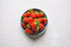 Ώριμες φράουλες σε ένα κύπελλο σε έναν άσπρο πίνακα Στοκ εικόνα με δικαίωμα ελεύθερης χρήσης