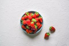 Ώριμες φράουλες σε ένα κύπελλο σε έναν άσπρο πίνακα Στοκ φωτογραφία με δικαίωμα ελεύθερης χρήσης