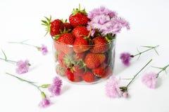 Ώριμες φράουλες σε ένα φλυτζάνι γυαλιού με μια ανθοδέσμη των ρόδινων λουλουδιών Στοκ Φωτογραφίες