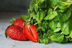 Ώριμες juicy φράουλες με μια δέσμη της ευώδους φρέσκιας μέντας σε ένα μπλε υπόβαθρο Πράσινα και φρούτα στοκ φωτογραφίες με δικαίωμα ελεύθερης χρήσης