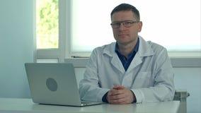 Ώριμη αρσενική συνεδρίαση γιατρών στο γραφείο με το lap-top και εξέταση τη κάμερα στο γραφείο κλινικών του Στοκ φωτογραφία με δικαίωμα ελεύθερης χρήσης