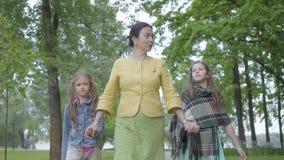 Ώριμη γιαγιά πορτρέτου που περπατά στο όμορφο πράσινο πάρκο με δύο χαριτωμένες εγγονές που κρατούν τα χέρια με τους και φιλμ μικρού μήκους