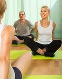 Ώριμη γιόγκα άσκησης ζευγών με τον εκπαιδευτικό Στοκ εικόνα με δικαίωμα ελεύθερης χρήσης