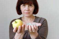Ώριμη γυναίκα με τα χάπια και Apple Στοκ Εικόνα