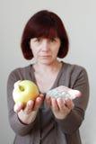 Ώριμη γυναίκα με τα χάπια και Apple Στοκ φωτογραφία με δικαίωμα ελεύθερης χρήσης