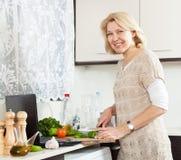 Ώριμη γυναίκα με τη μαγειρεύοντας σούπα σημειωματάριων στην εγχώρια κουζίνα Στοκ φωτογραφίες με δικαίωμα ελεύθερης χρήσης