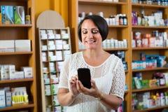 Ώριμη γυναίκα με το τηλέφωνο στο φαρμακείο στοκ εικόνα