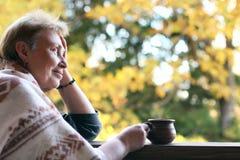 Ώριμη γυναίκα με το φλυτζάνι του καυτού ποτού και του μάλλινου καρό στο te στοκ εικόνα με δικαίωμα ελεύθερης χρήσης