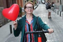 Ώριμη γυναίκα που αγαπά το ηλεκτρικό μηχανικό δίκυκλό της στοκ φωτογραφία με δικαίωμα ελεύθερης χρήσης