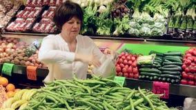 Ώριμη γυναίκα που αγοράζει τα πράσινα φασόλια στην αγορά απόθεμα βίντεο