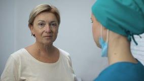 Ώριμη γυναίκα που ακούει τα αποτελέσματα της δοκιμής από το γιατρό, υποψία της κακής διάγνωσης απόθεμα βίντεο