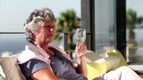 Ώριμη γυναίκα που απολαμβάνει το ποτήρι του κρασιού στο μπαλκόνι απόθεμα βίντεο