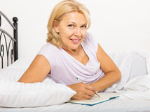 Ώριμη γυναίκα που γράφει στο ημερολόγιο στοκ φωτογραφία