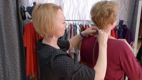 Ώριμη γυναίκα που δοκιμάζει την αλυσίδα περιδεραίων στη μπουτίκ εξαρτημάτων Πωλητής που βοηθά να δοκιμάσει το κομψό περιδέραιο στ απόθεμα βίντεο