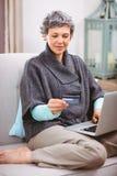 Ώριμη γυναίκα που εξετάζει την πιστωτική κάρτα χρησιμοποιώντας το lap-top Στοκ Εικόνες