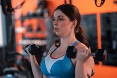 Ώριμη γυναίκα που επιλύει στη γυμναστική που χρησιμοποιεί barbells στοκ εικόνα με δικαίωμα ελεύθερης χρήσης