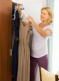 Ώριμη γυναίκα που επιλέγει το φόρεμα στο σπίτι Στοκ εικόνες με δικαίωμα ελεύθερης χρήσης