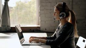 Ώριμη γυναίκα που εργάζεται στο τηλεφωνικό κέντρο που χρησιμοποιεί την κάσκα φιλμ μικρού μήκους