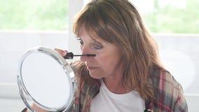 Ώριμη γυναίκα που εφαρμόζει mascara στα eyelashes απόθεμα βίντεο
