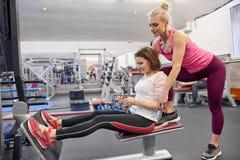 Ώριμη γυναίκα που κάνει τις αθλητικές ασκήσεις με τον προσωπικό εκπαιδευτή στη γυμναστική Θηλυκή βοηθώντας ηλικιωμένη γυναίκα εκπ στοκ φωτογραφία με δικαίωμα ελεύθερης χρήσης