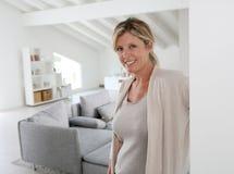 Ώριμη γυναίκα που καλωσορίζει στο σπίτι τους φιλοξενουμένους στη μπροστινή πόρτα Στοκ Εικόνες