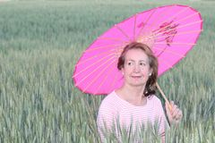 Ώριμη γυναίκα που κρατά μια ρόδινη ομπρέλα κατά τη διάρκεια της ηλιόλουστης ημέρας στοκ φωτογραφίες με δικαίωμα ελεύθερης χρήσης