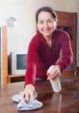 Ώριμη γυναίκα που ξεσκονίζει τον ξύλινο πίνακα Στοκ φωτογραφία με δικαίωμα ελεύθερης χρήσης
