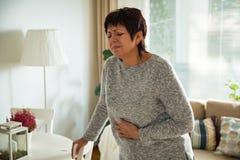 Ώριμη γυναίκα που πάσχει από τον πόνο στομαχιών Στοκ Φωτογραφίες